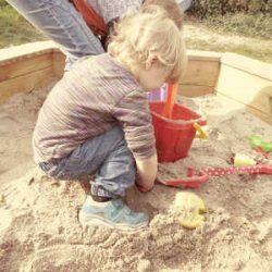 drieling jongetje speelt in zandbak